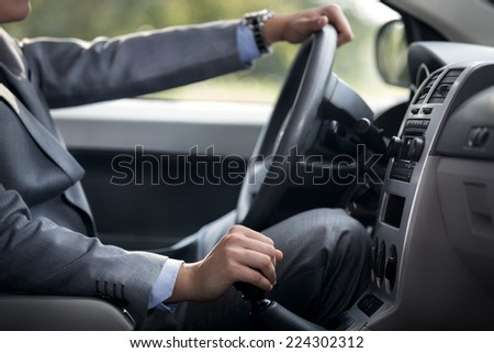 man driving car with hand on gearbox - stock photo