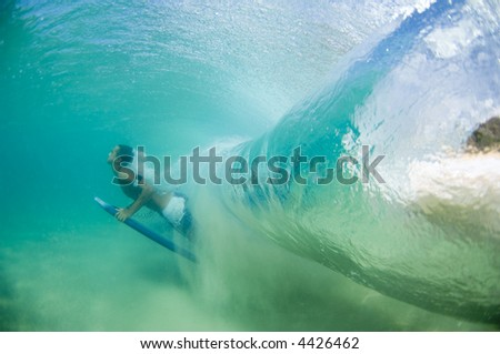man duck diving a giant wave in hawaii (editorial use only) - stock photo