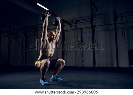 Man during workout gym. Squat with kettlebells over head - stock photo