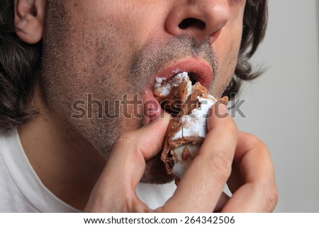 man eating a Cannolo, traditional Sicilian pastry - stock photo