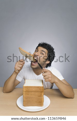 Man eating a slice of bread - stock photo