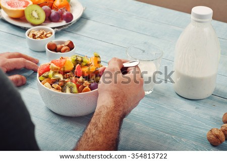 Man eating breakfast fruit salad with yogurt. Top view with copy space - stock photo