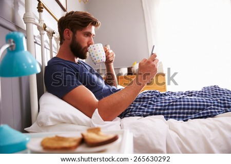 Man Eating Breakfast In Bed Whilst Using Mobile Phone - stock photo
