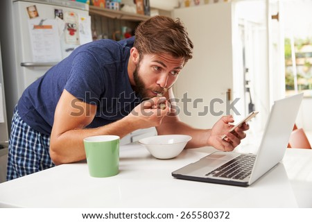 Man Eating Breakfast Whilst Using Mobile Phone And Laptop - stock photo
