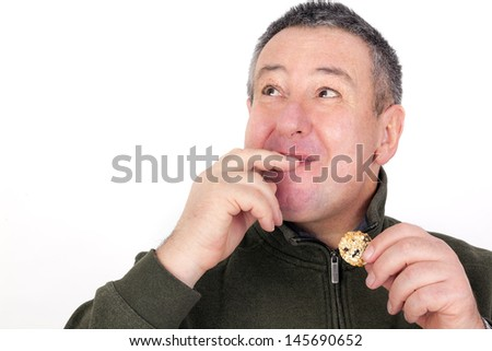 Man eating cookies and licks his fingers - stock photo