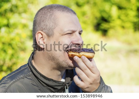 Man eating donuts - stock photo