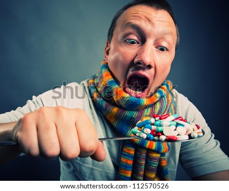 Man eating pills and medicines with big spoon - stock photo