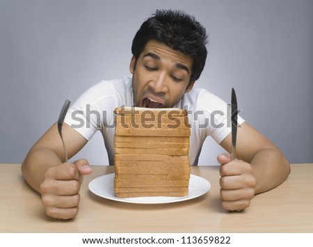 Man eating slices of bread - stock photo