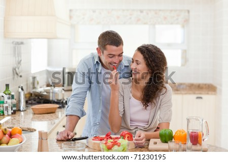Man eating vegetables with his wife at home - stock photo