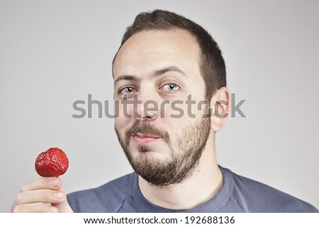 Man eats strawberry - stock photo