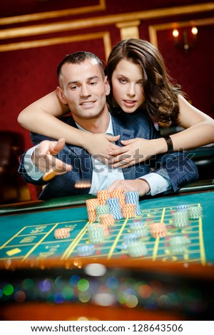 Man embraced by pretty girl throws the chip on the playing table - stock photo