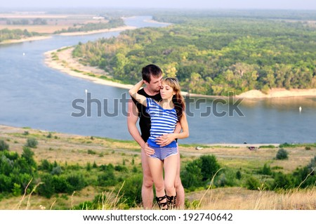 Man embraces the girl on a background of beautiful scenery - stock photo