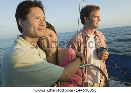 Man embracing a smiling woman by friend on sailboat - stock photo