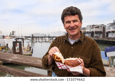 Man Enjoying Chowder in a sour dough bread bowl -San Francisco on the pier - stock photo