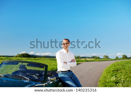 Man enjoying his freedom standing in lush green countryside leaning on his cabriolet car - stock photo