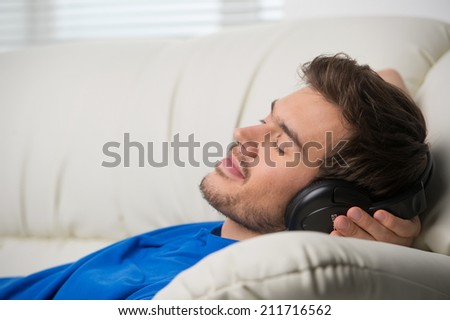 Man enjoying music lying on couch. Dreaming man listening to music at home - stock photo