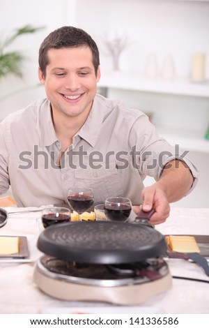 Man enjoying raclette at home with friends - stock photo