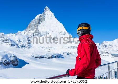 man enjoying the view over the beautiful landscape of winter mountains. Matterhorn. Swiss. Winter vacation - stock photo