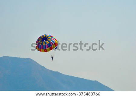 man enjoys on the parachute in the sky over the sea and mountain - stock photo