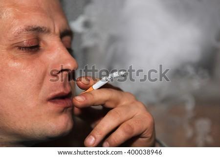 Man enjoys tobacco smoke - stock photo