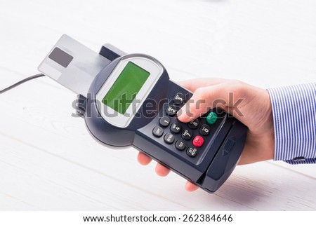 Man entering his pin on terminal on a wooden table