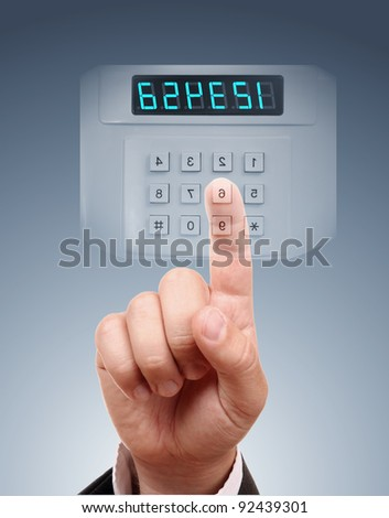 Man entering safe or door code - stock photo