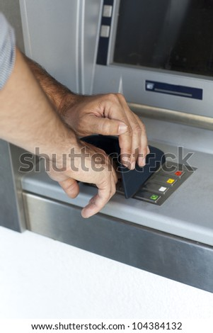 Man enters the PIN number at the ATM - stock photo