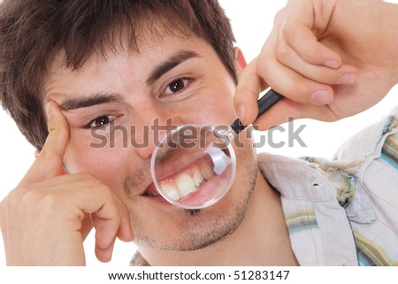 Man examining his teeth with magnifier - stock photo
