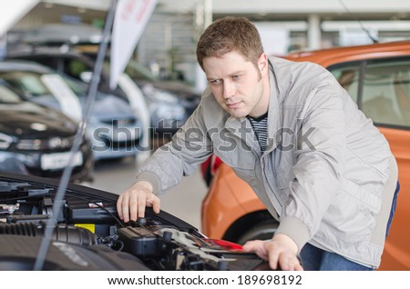 Man examining new car at the dealership.