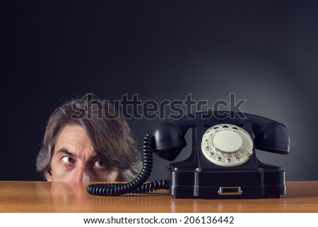 Man exasperated looks on retro phone. - stock photo