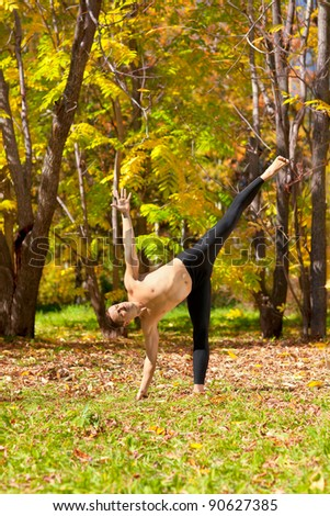 Man exercises in the autumn forest yoga Ardha chandrasana pose - stock photo