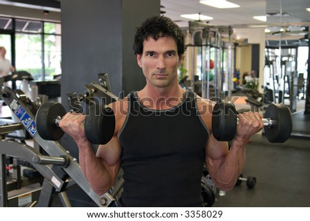 Man exercising his arm muscles by lifting two dumbell free weights in a fitness club. - stock photo