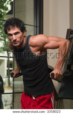 Man exercising his arm muscles on an exercise machine in a fitness center. - stock photo