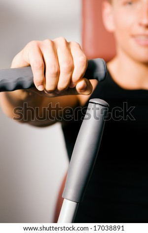 Man exercising in the gym (focus on his hand at the handles!) - stock photo
