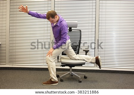 man exercising on chair in office, healthy lifestyle  - profile view - stock photo