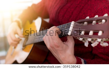 Man exercising playing acoustic guitar at home