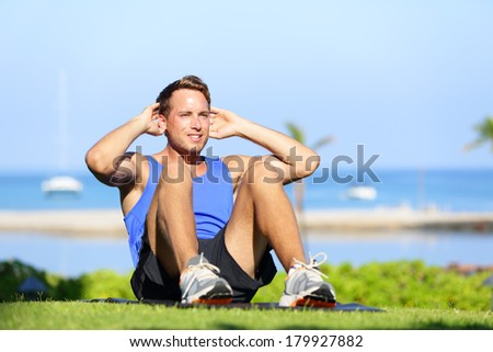 Man exercising sit-ups outside. Male fitness model training situps exercise outdoor in summer during workout. Handsome fit muscular sport model. - stock photo