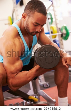 Man exercising with dumbbells at a gym, vertical shot - stock photo