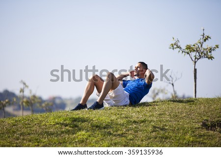 Man exercising with sit ups at Lisbon - stock photo