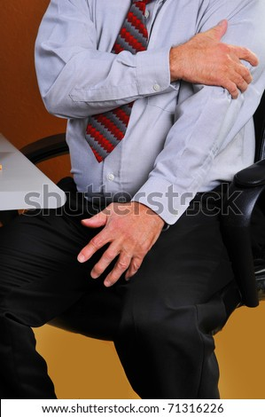 Man experiencing pain in his left arm which may be a sign of a heart attack. His poor looking health may be a contributing factor as men with large stomachs have a greater chance of heart disease. - stock photo