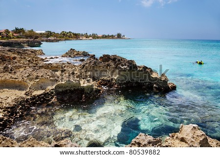 Man explores the reef off the rocky (Ironshore formation) areas of Smith Cove, Grand Cayman. Slight curve to the horizon - stock photo