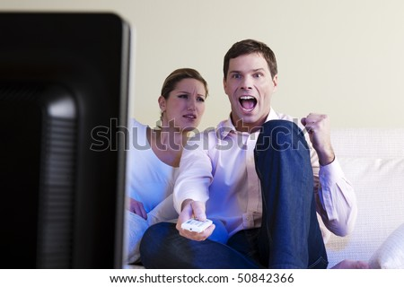 Man exulting watching tv, woman disappointed - stock photo
