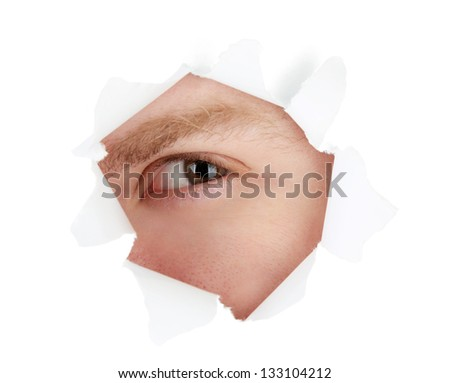 Man eye looking through hole in sheet of paper