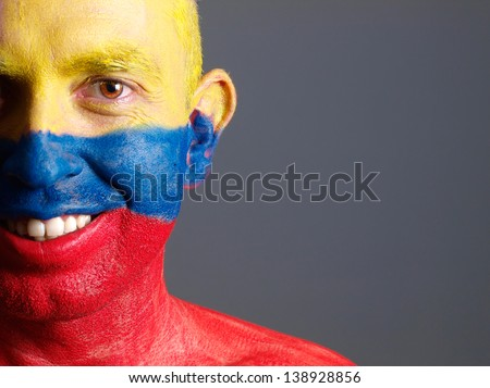 Man face painted with colombian flag. The man is smiling and photographic composition leaves only half of the face. - stock photo