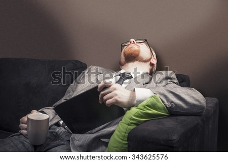 Man Fallen Asleep on Home Sofa While Holding Coffee and Tablet
