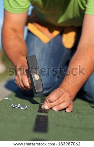 Man fastening the bitumen roof shingles - closeup on hands with hammer and nails - stock photo