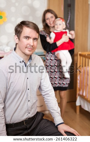 Man father in bedroom with his wife and daughter