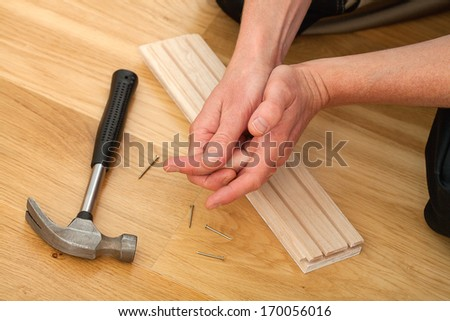 Man feeling his sore hand after having hurt himself while hammering - stock photo