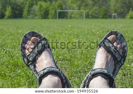 Man feet laying on the green grass of play-field - stock photo