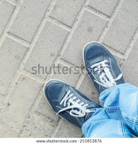 man feet on cobbled road - stock photo